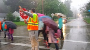 The Walking School Bus crosses Normal St with the help of a crossing guard.