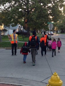 A Truman football player serves as a crossing guard to help a Walking School Bus cross Cottage Grove.